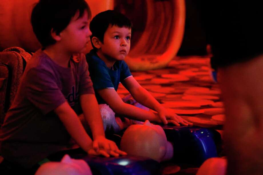 Sean Wyker, 4, left, and his brother Liam, 5, listen to medical-student instructors as they learn how to do chest compressions during National Texas Two Step's CPR training at The Health Museum in Houston on Sunday. Photo: Michael Ciaglo, Houston Chronicle / Michael Ciaglo