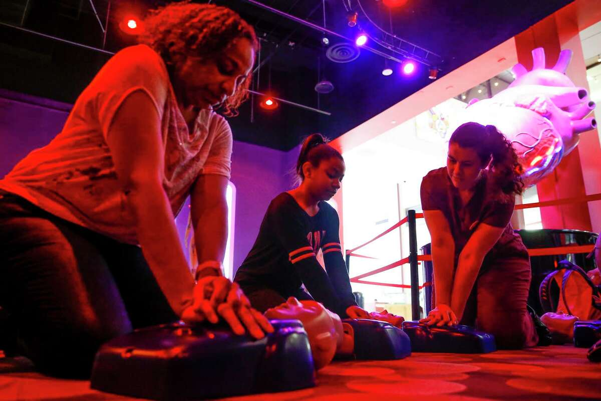 University of Texas medical student Regan Puckett, right, teaches Stacy Gant and her daughter, Kennedy, 9, the two steps that can help save a life - calling 911 and compression-only CPR - at The Health Museum in Houston on Sunday.
