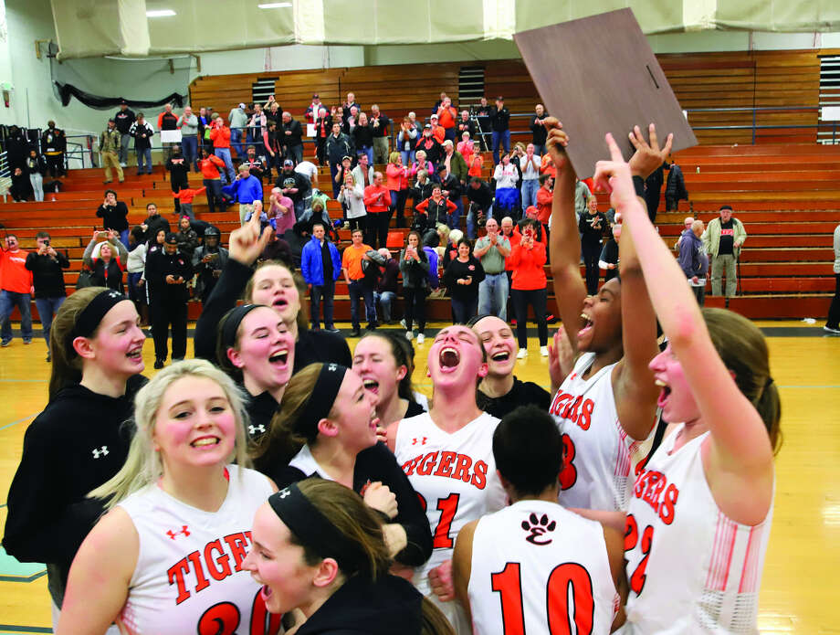 The Edwardsville girls' basketball team celebrates after winning the Class 4A Champaign Centennial Sectional championship with a victory over Rock Island on Thursday. Photo: By Rick Brewer