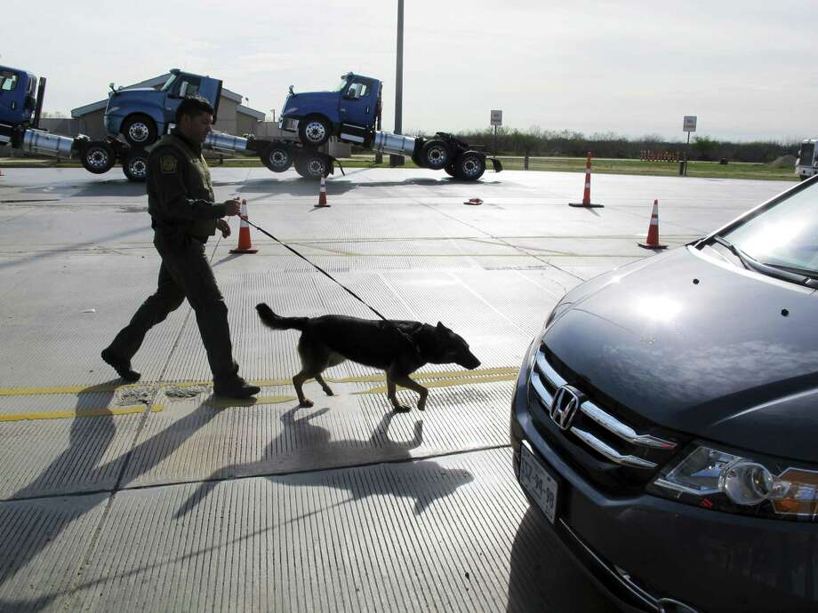 A Border Patrol agent uses a dog to inspect vehicles lining up at the Laredo North vehicle checkpoint in Laredo, Texas, on Friday, Feb. 2, 2018. The Border Patrol estimates that about 9,000 vehicles pass through their checkpoint every day, many coming north from Mexico. Photo: Nomaan Merchant / Associated Press / Copyright 2018 The Associated Press. All rights reserved.