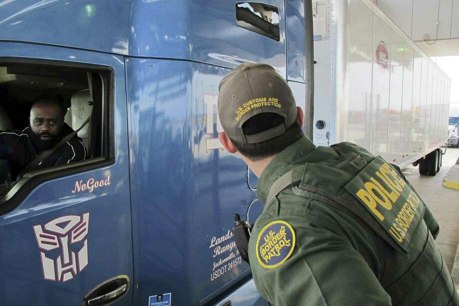 Border Patrol agent Eric Mendoza speaks to the driver of a tractor-trailer waiting to pass through the Laredo North vehicle checkpoint in Laredo, Texas, on Friday, Feb. 2, 2018. Agents say the checkpoint is sometimes overwhelmed by traffic, making it a certainty that some smugglers get through. Photo: Nomaan Merchant / Associated Press / Copyright 2018 The Associated Press. All rights reserved.