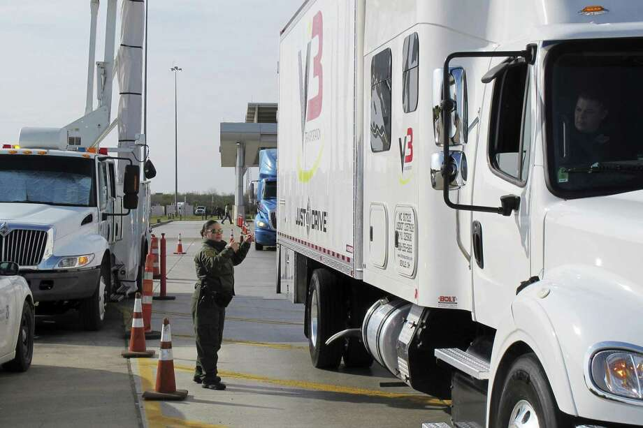 Border Patrol agent Gracie Briones waves through a tractor-trailer after it passed through an X-ray machine at the Laredo North checkpoint in Laredo, Texas, on Friday, February 2, 2018. Only a fraction of tractor-trailers undergo a scan in by the machine, which allows agents to check for any signs of humans or drugs hidden inside. (AP Photo/Nomaan Merchant) Photo: Nomaan Merchant, STF / Associated Press / Copyright 2018 The Associated Press. All rights reserved.