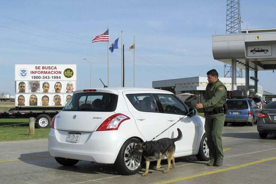A Border Patrol agent uses a dog to inspect a car waiting to pass through the Laredo North vehicle checkpoint in Laredo, Texas, on Friday, February 2, 2018. The dogs are trained to catch drugs and people who try to enter the U.S. illegally in trunks and vehicle compartments. (AP Photo/Nomaan Merchant) Photo: Nomaan Merchant, STF / Associated Press / Copyright 2018 The Associated Press. All rights reserved.