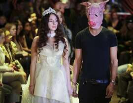 Sabrina Piper, 21, left, stands handcuffed to a male model costumed as a pig, during the #MeToo fashion show, at Fashion Week, Friday Feb. 9, 2018, in New York. Piper joined a small group of sexual misconduct survivors using the #MeToo moment and fashion to share their stories and empower other survivors. (AP Photo/Bebeto Matthews)