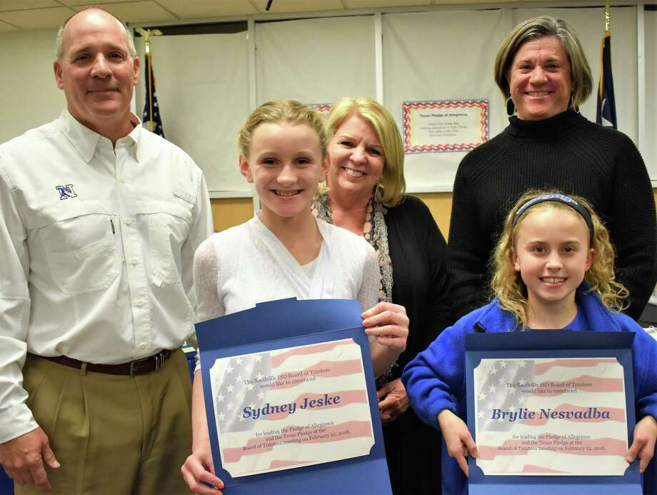 Needville Middle School students Sydney Jeske, front left, and Brylie Nesvadba, front right, led those in attendance in the Pledge of Allegiance at the Feb. 12 school board meeting. In back are, from left, Superintendent Curtis Rhodes, Assistant Superintendent of Finance Dovie Peschel and Assistant Superintendent Beth Briscoe. Photo: Needville ISD