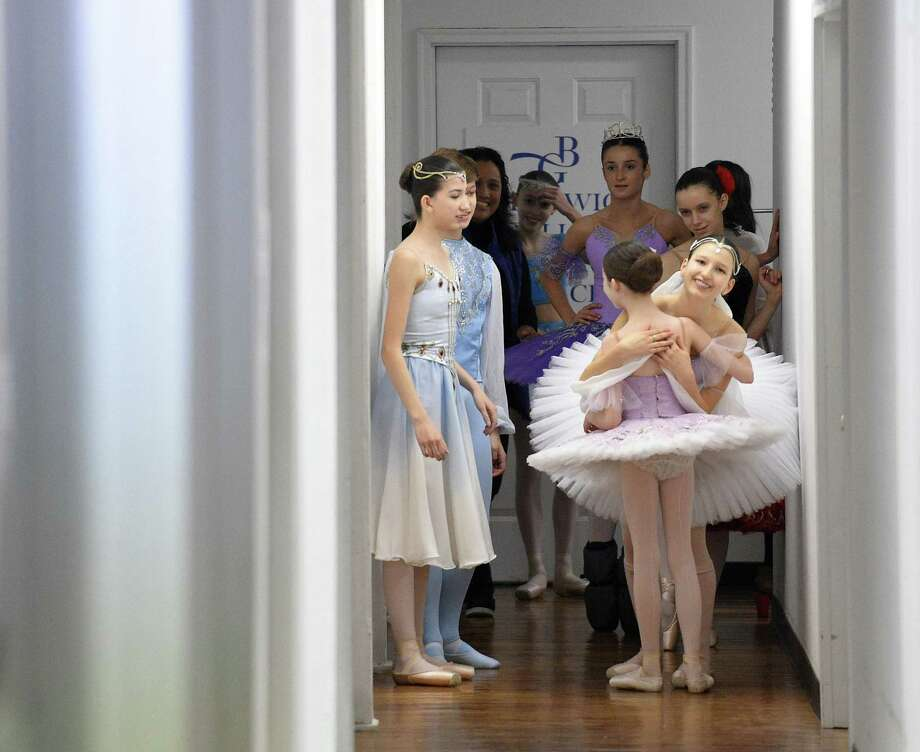 Carolina Rivera hugs a young dancer as fellow dancers prepare to  perform in a mini-showcase of the Greenwich Ballet Academy dancers on Saturday, Feb. 24, 2018 in Port Chester, New York. The dancers are preparing for the upcoming semi-finals for the YAGP competition, an international ballet competition held in Boston and New York. Photo: Matthew Brown / Hearst Connecticut Media / Stamford Advocate
