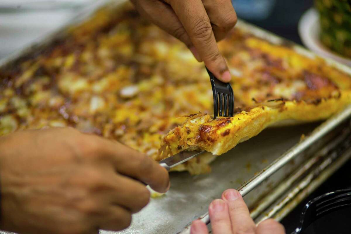 Pizza is sliced for the judges during the judging of the Gold Buckle Foodie Awards in the Main Club of NRG Center, Monday, Feb. 26, 2018, in Houston. Judges tasted food that is available to the general public throughout the carnival and rodeo in several categories from