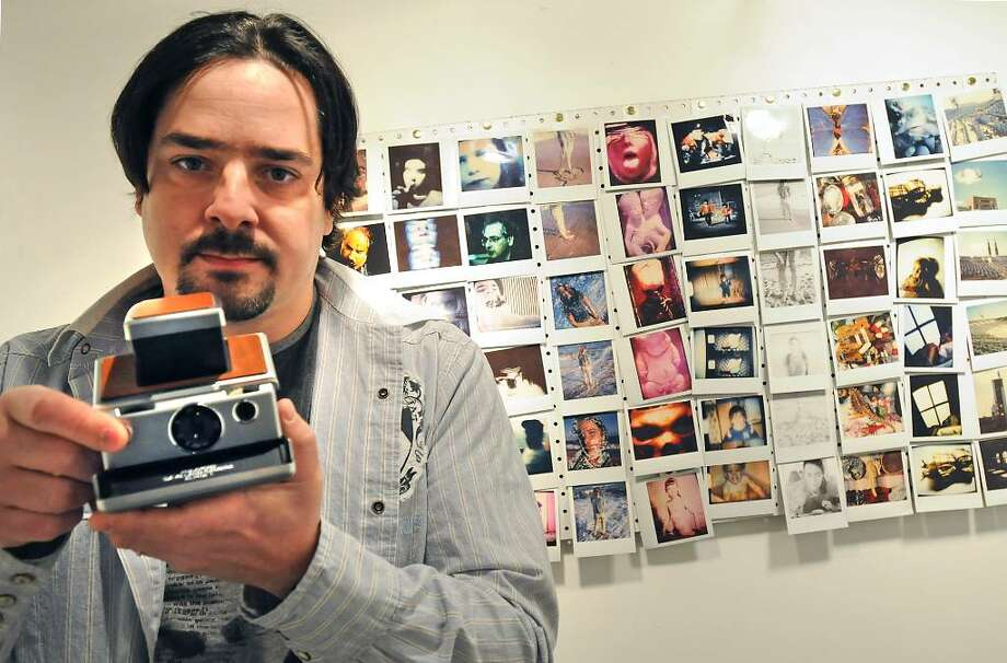 Artist Adam Furgang stands next to his polaroid exhibit holding his polaroid camera at the Upstate Artist Guild on Lark Street in Albany, NY on January 7, 2010. For Preview section. (Lori Van Buren / Times Union) Photo: LORI VAN BUREN