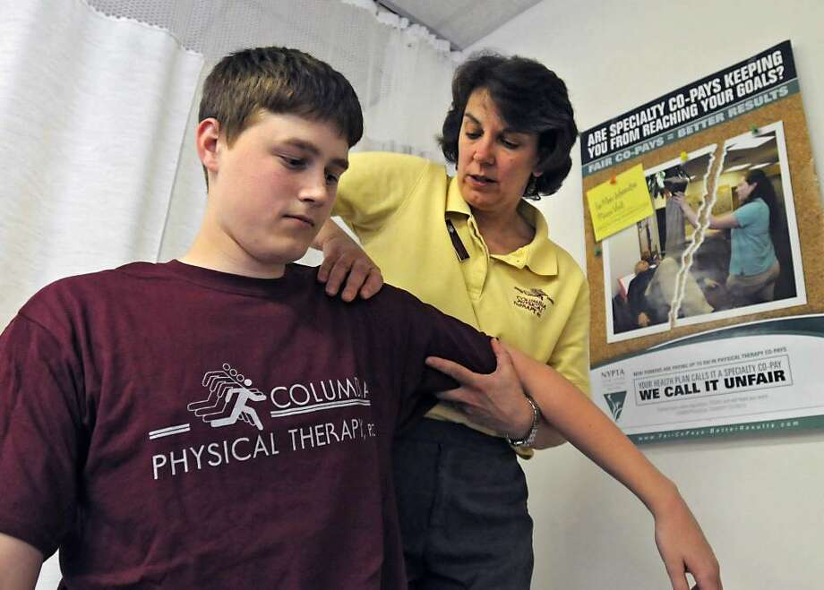 Physical Therapist Doreen Frank works with Maple Hill High School athlete Joe Chipman, 17, of Schodack, at Columbia Physical Therapy in East Greenbush.  Physical therapy co-pays are rising and discouraging some patients from seeking care, but insurance industry advocates oppose legislation seeking caps. (Lori Van Buren/Times Union) Photo: LORI VAN BUREN