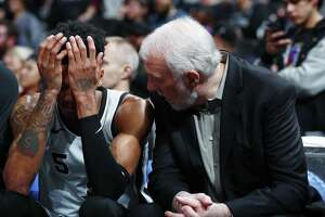 San Antonio Spurs guard Dejounte Murray (5) and San Antonio Spurs head coach Gregg Popovich confer in the second half of an NBA basketball game Tuesday, Feb. 13, 2018, in Denver. The Nuggets won 117-109. (AP Photo/David Zalubowski)