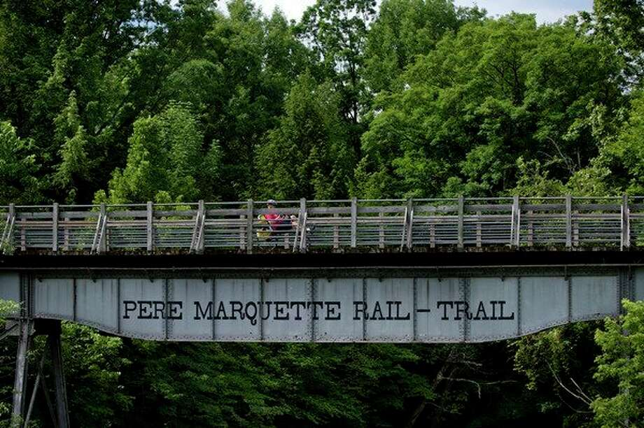 FILE — A cyclist on a recumbent bicycle crosses over the Tittabawassee River on the Pere Marquette Rail-Trail near Quarter Line Road in Midland County. (Daily News file photo)  / Midland Daily News