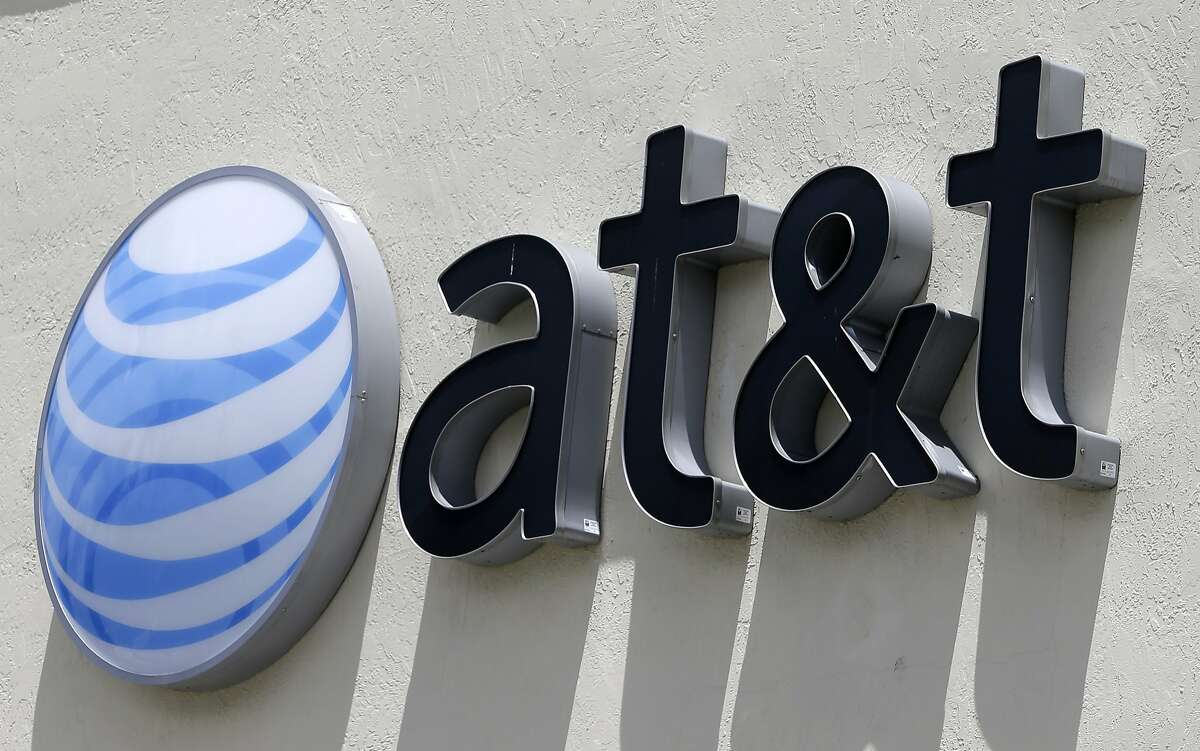 This July 27, 2017, file photo shows an AT&T logo at a store in Hialeah, Fla.