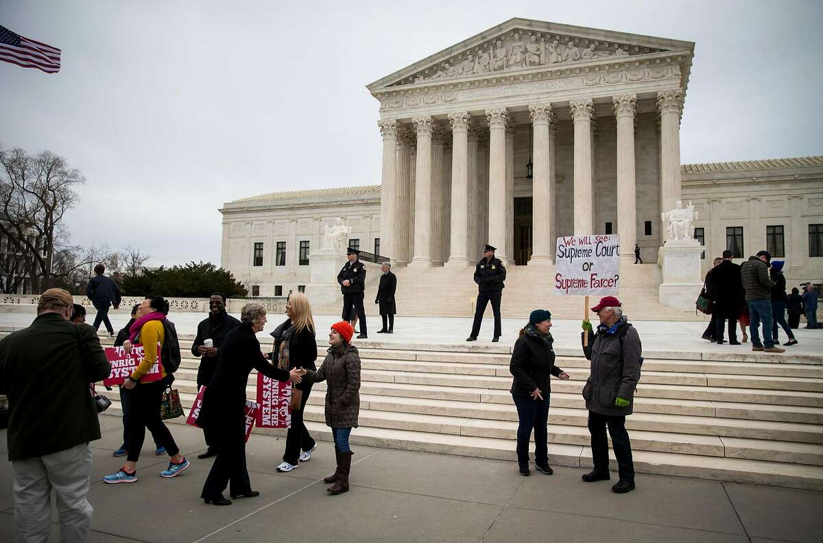 People gather outside of the Supreme Court in Washington, Feb. 26, 2018. The Supreme Court on Monday declined to clear the way for the Trump administration to end the Obama-era program that protects about 700,000 young immigrants from deportation, meaning that the so-called