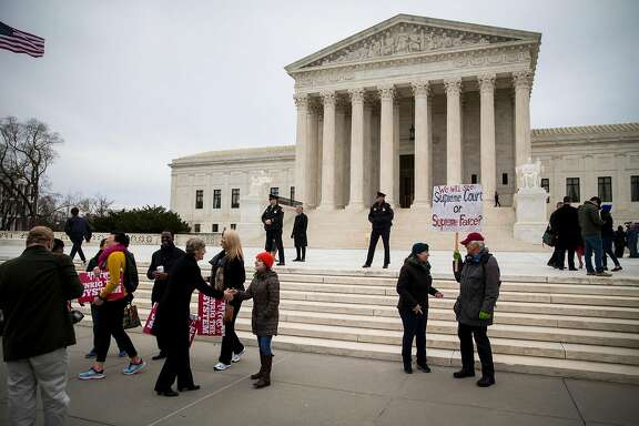 """People gather outside of the Supreme Court in Washington, Feb. 26, 2018. The Supreme Court on Monday declined to clear the way for the Trump administration to end the Obama-era program that protects about 700,000 young immigrants from deportation, meaning that the so-called """"Dreamers"""" could remain in legal limbo for many months unless Congress acts to make their status permanent. (Al Drago/The new York Times)"""