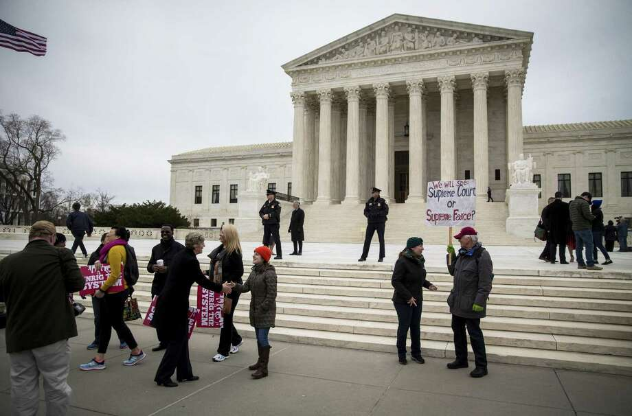 People gather outside of the Supreme Court in Washington on Monday. The Supreme Court on Monday declined to clear the way for the Trump administration to end the Obama-era program that protects about 700,000 young immigrants — Dreamers — from deportation. But congressional action is still needed. Photo: AL DRAGO /NYT / NYTNS