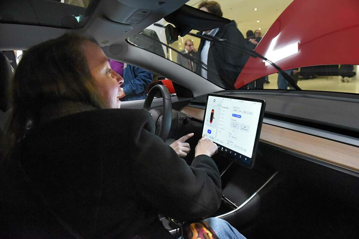 Linda Herman of Hopewell Junction, foreground, and her sister-in-law Sue Herman of Salt Point, in driver seat, check out the newest Model 3 Tesla during TeslaOs Model 3 Road Trip and Policy Forum at the Empire State Plaza Concourse on Monday, Feb. 26, 2018 in Albany, N.Y. (Lori Van Buren/Times Union)