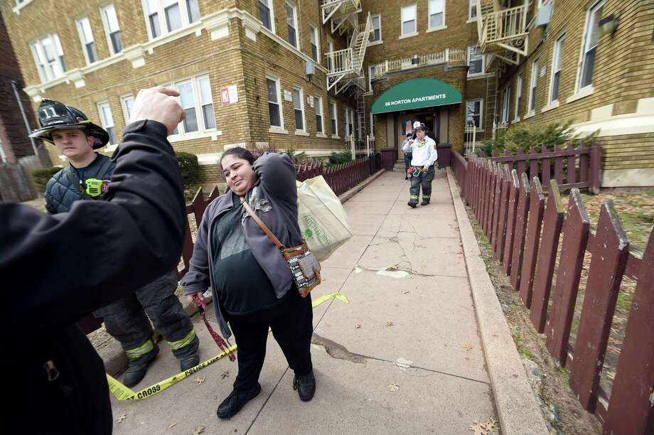 Vanessa Grassi, center, returned to her apartment on the fifth floor of 66 Norton Apartments to retrieve her sleep apnea machine and  diabetes medication Monday in New Haven . Grassi lived there with her two children. Photo: Arnold Gold / Hearst Connecticut Media / New Haven Register