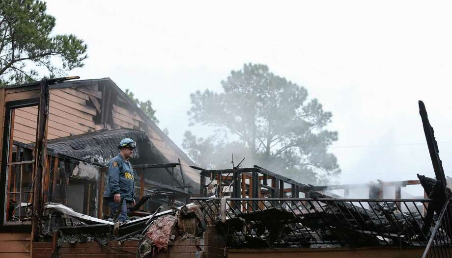 An arson investigator from the Harris County Fire Marshal's Office walks through debris after a three-alarm fire at the North Bend Apartments complex Monday, Feb. 26, 2018, in Houston. Sixteen units were damaged in the three-alarm fire Monday morning. Photo: Godofredo A. Vasquez / Godofredo A. Vasquez / Houston Chronicle