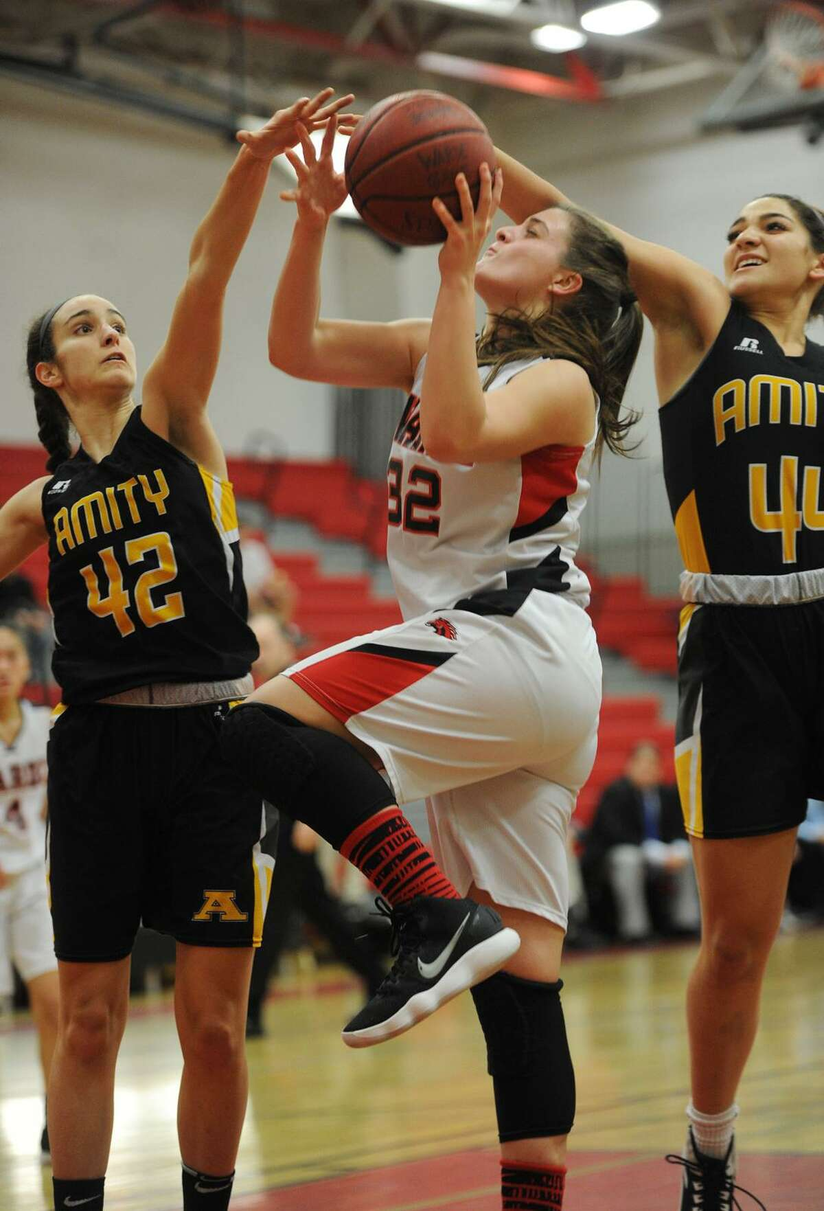 Warde's Olivia Parisi tries to shoot through the blocks of Amity defenders Amanda Granados, left, and Hayley Esparo in the first half of Monday night's game at Warde High School in Fairfield.