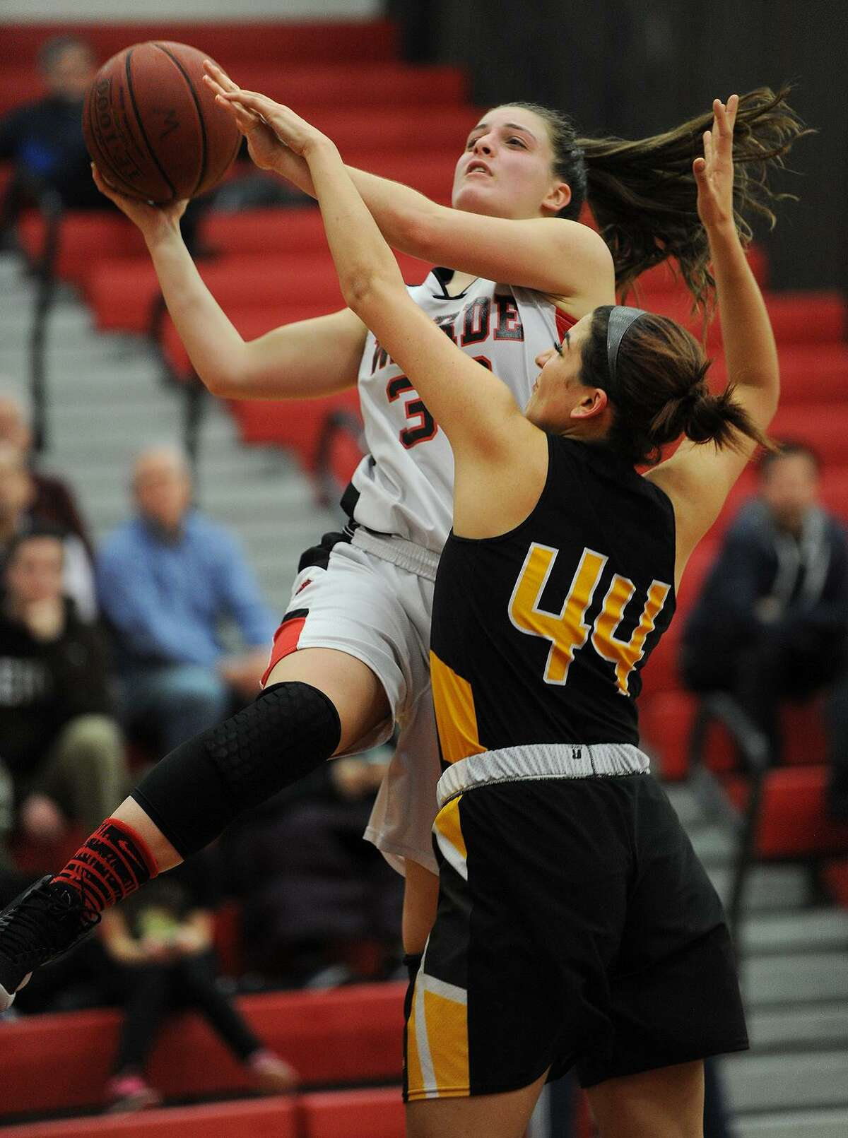 Warde's Olivia Parisi drives to the basket against Amity defender Hayley Esparo in the second half of Monday night's game at Warde High School in Fairfield.