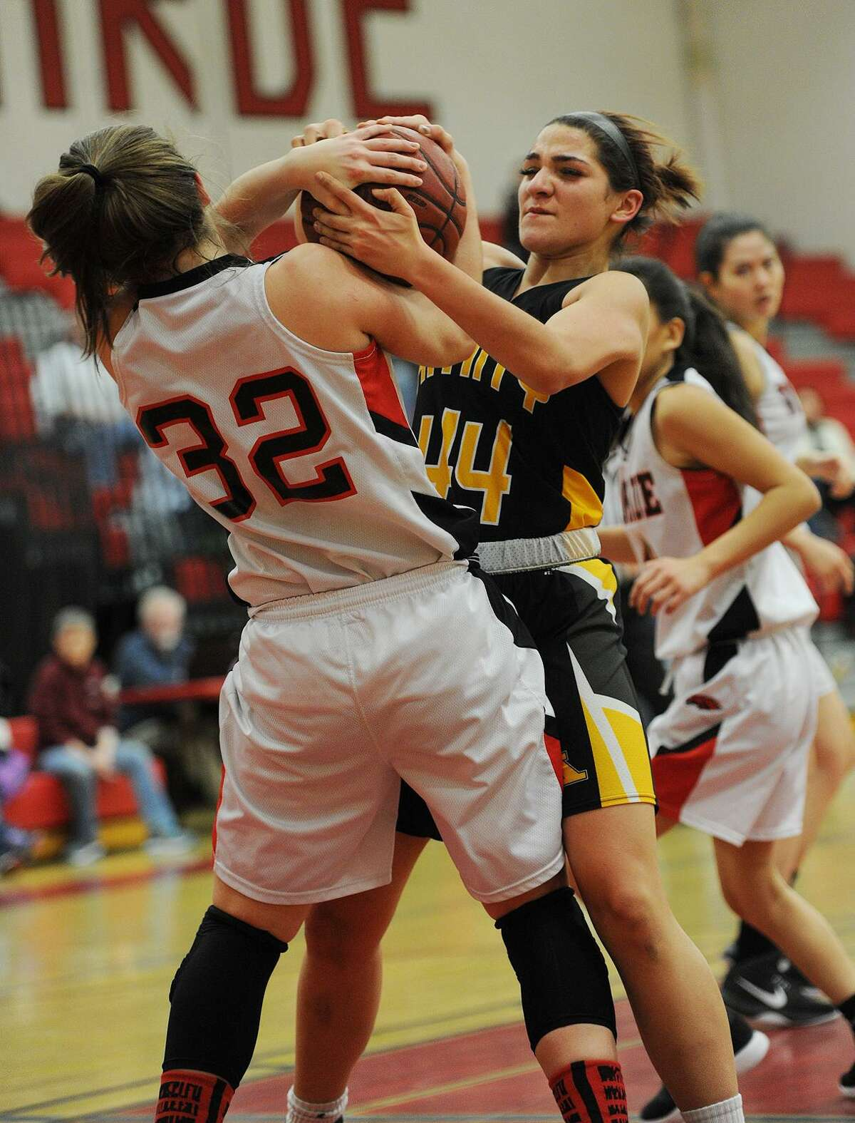 Warde's Olivia Parisi, left, battles for a rebound with Amity's Hayley Esparo in the first half of Monday night's game at Warde High School in Fairfield.