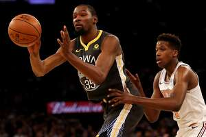 NEW YORK, NY - FEBRUARY 26:  Kevin Durant #35 of the Golden State Warriors passes as Frank Ntilikina #11 of the New York Knicks defends at Madison Square Garden on February 26, 2018 in New York City. NOTE TO USER: User expressly acknowledges and agrees that, by downloading and or using this Photograph, user is consenting to the terms and conditions of the Getty Images License Agreement  (Photo by Elsa/Getty Images)