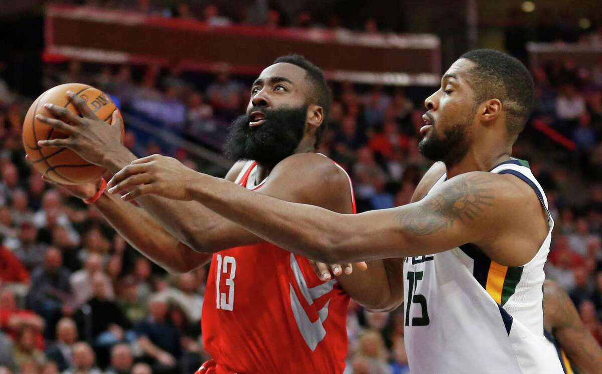 Houston Rockets guard James Harden (13) goes to the basket as Utah Jazz forward Derrick Favors (15) defends in the first half during an NBA basketball game Monday, Feb. 26, 2018, in Salt Lake City. (AP Photo/Rick Bowmer)