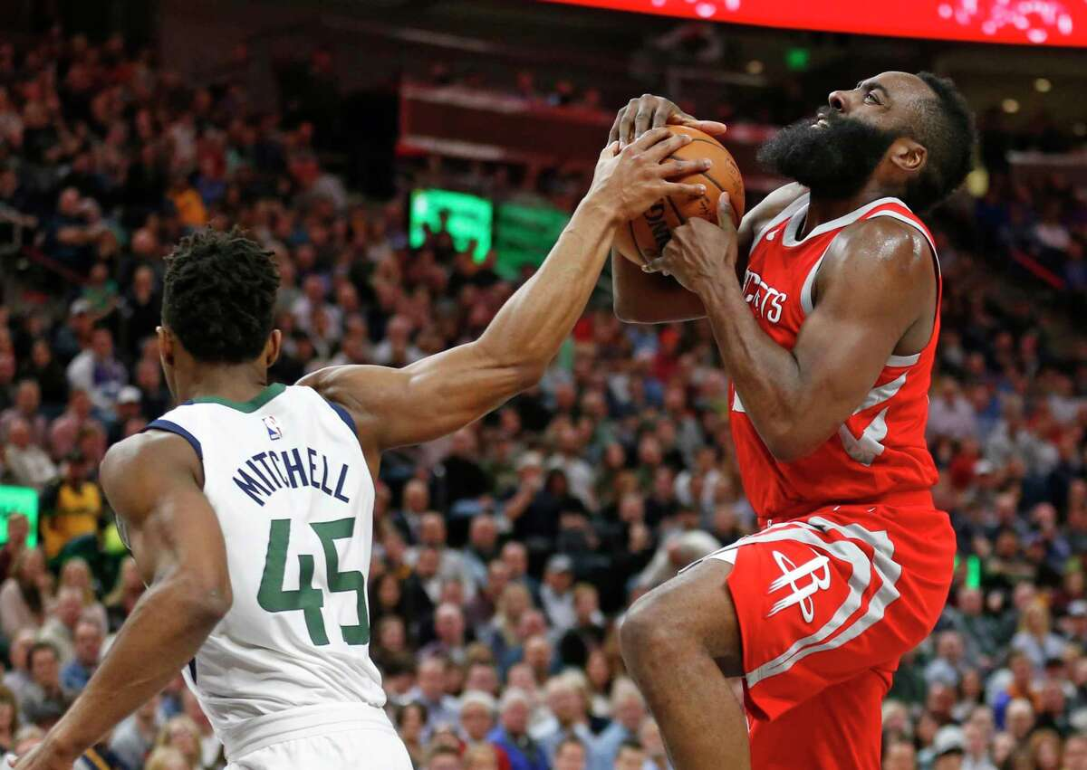 Utah Jazz guard Donovan Mitchell (45) defends against Houston Rockets guard James Harden, right, as he drives to the basket in the first half during an NBA basketball game Monday, Feb. 26, 2018, in Salt Lake City. (AP Photo/Rick Bowmer)