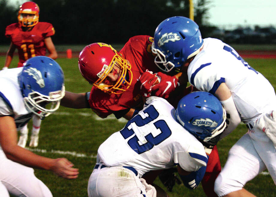 Roxana's Talon Pile (center) gets locked up by Greenville's Christian Moss (left), Brady Simpson (23) and Ryan Hutchinson during Pile's kick return Friday night at Raich Field in Roxana. James B. Ritter / For The Telegraph