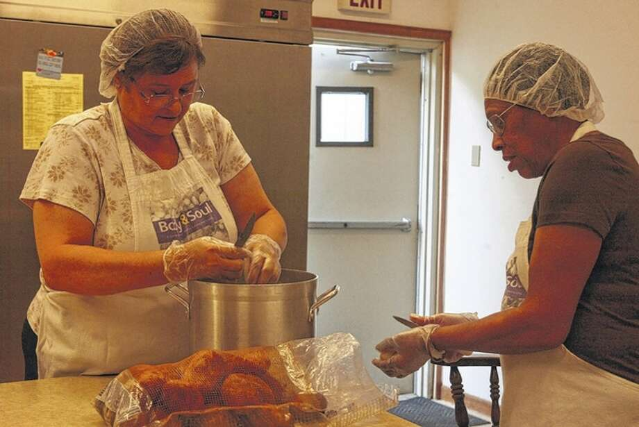 Kim Edmondes (left) and Otha Mae Davis prepare food at the Spirit of Faith Church on Tuesday in preparation for a soup kitchen that provides meals for those in need. Samantha McDaniel-Ogletree | Journal-Courier