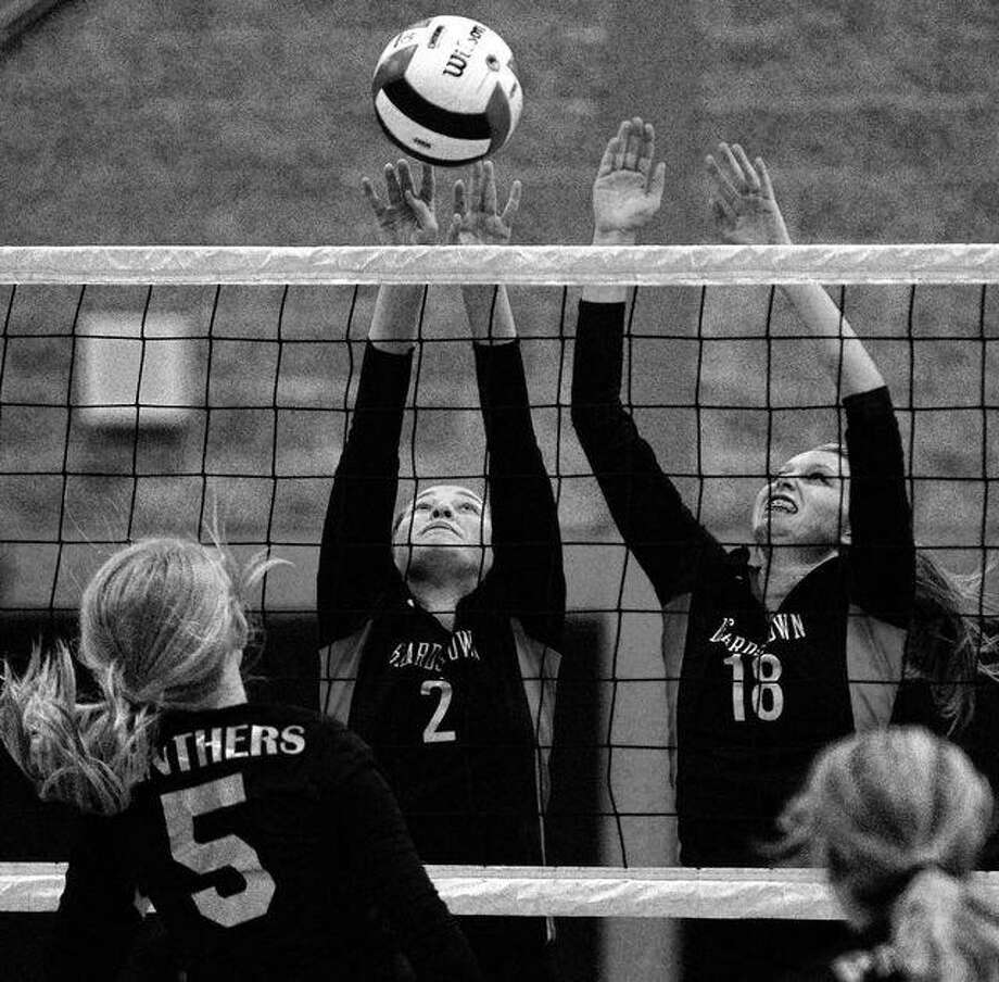 Beardstown's Savannah Price (2) and Olivia Dour (18) try to block a spike during a match against Camp Point Central in the semifinals of the Beardstown Regional Tuesday night. Dennis Mathes | Journal-Courier
