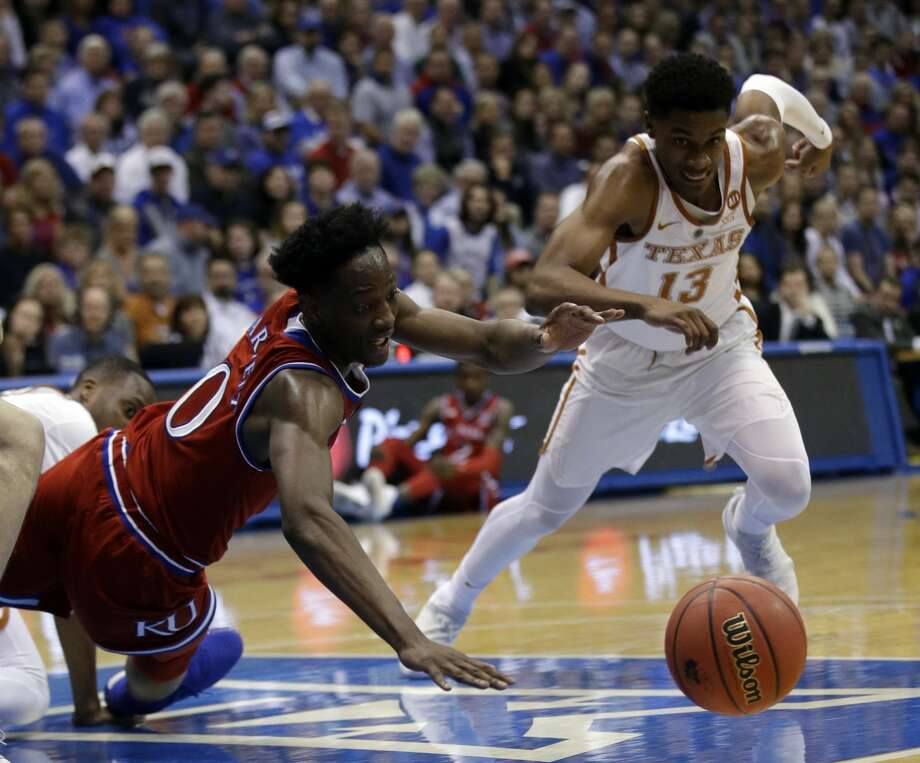 Kansas guard Marcus Garrett (0) dives for the ball ahead of Texas guard Jase Febres, right, during the first half of an NCAA college basketball game against Texas in Lawrence, Kan., Monday, Feb. 26, 2018. Kansas defeated Texas 80-70. (AP Photo/Orlin Wagner) Photo: Orlin Wagner/Associated Press
