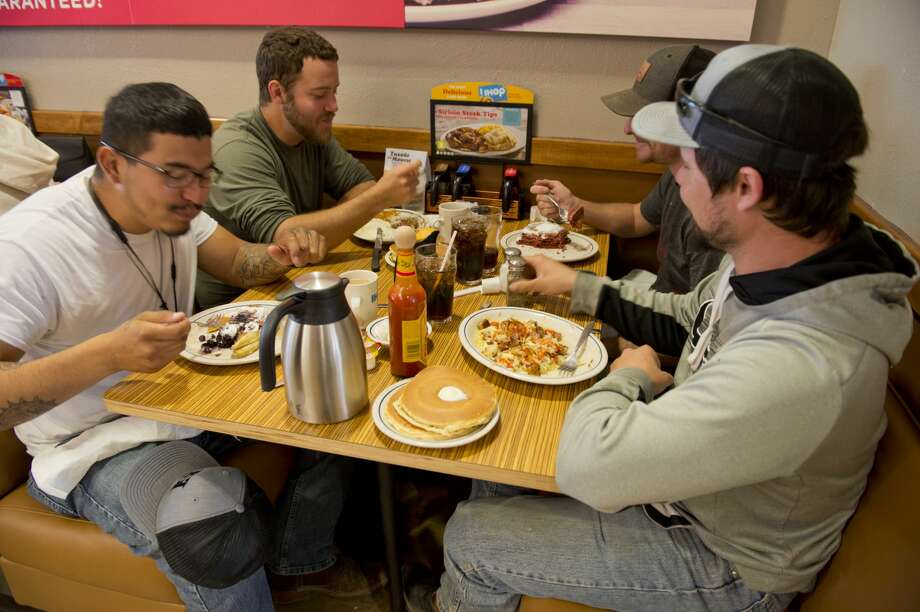 Novel Martinez, from left, Derek Greetan, Lance Lessard and Jeremiah Polito enjoy free pancakes at IHOP on Feb. 27, National Pancake Day. The restaurant has temporarily changed its name to IHOb – International House of burgers -- in an effort to call attention to its burger menu. Photo: Tim Fischer/Midland Reporter-Telegram
