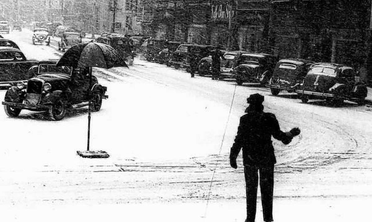 Snow, welcomed only by dreamers and anxious children, caused many problems in the city of Alton. The steep hills and snow are still not compatible. Altonians manage to go on about their business during most snowstorms. A downtown scene in the 1930s leaves one feeling sorry for the traffic policeman who needs to keep the traffic moving.