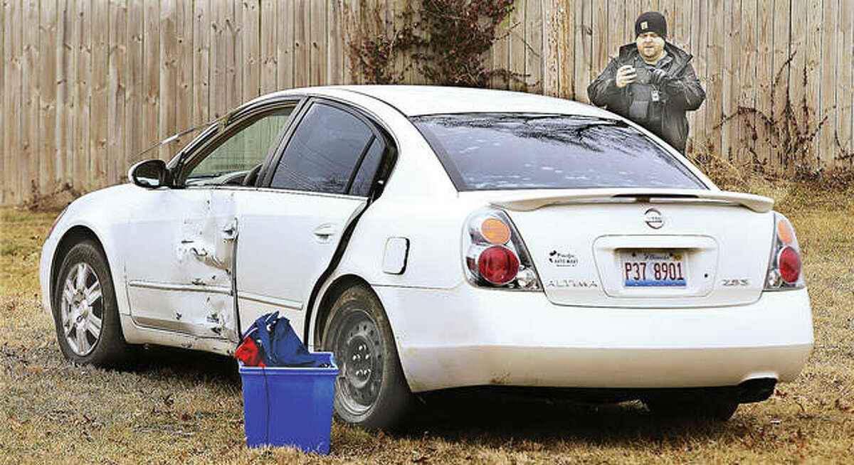 An officer photographs the white Nissan Altima and the damages done to it by a carjacker Thursday after he fled police, crashed into mailboxes and a small tree before running off into an open field in the 900 block of Missouri Street in South Roxana.