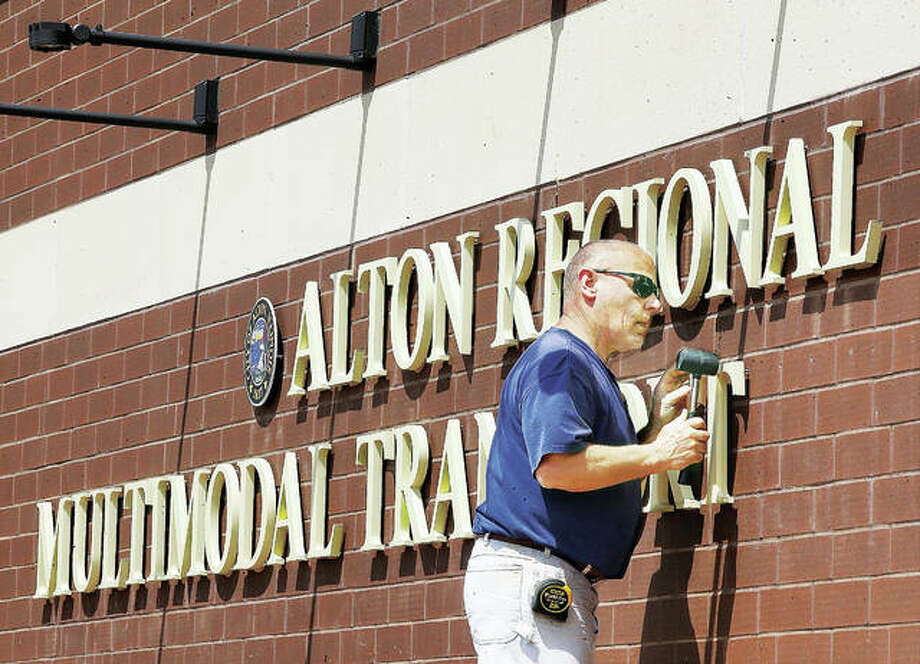 An employee of R.W. Boeker Co., Inc., in Hamel, uses a rubber mallot to tap a T into place for the lettering of the sign on the Alton Regional Multimodal Transportation Center last April. Photo: John Badman | The Telegraph