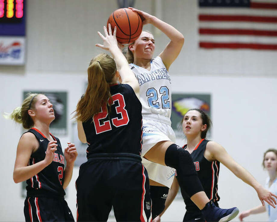 Jersey's Clare Breden (22) drives through Highland defenders (from left) Rece Portell, Lauren Baer and Ellie Brown and is fouled on her way to the hoop during a Mississippi Valley Conference game in Jerseyville on Thursday night. Breden, a freshman, scored a career-high 39 points in Jersey's double-overtime victory. Photo: Billy Hurst / For The Telegraph