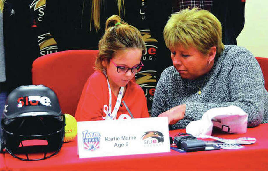 Karlie Maine, a 6-year-old from Alhambra, signs a national letter of intent to join the SIUE softball program on Thursday. The 'signing' was made possible by Team IMPACT, which according to its website, is a national non-profit organization that connects children facing serious and chronic illnesses to local college-athlete teams to form life-long bonds and life-changing outcomes. Karlie has battled a heart condition and other diseases since birth. Cougars coach Sandy Montgomery is seated with Maine. Photo: Matthew Kamp | For The Telegraph