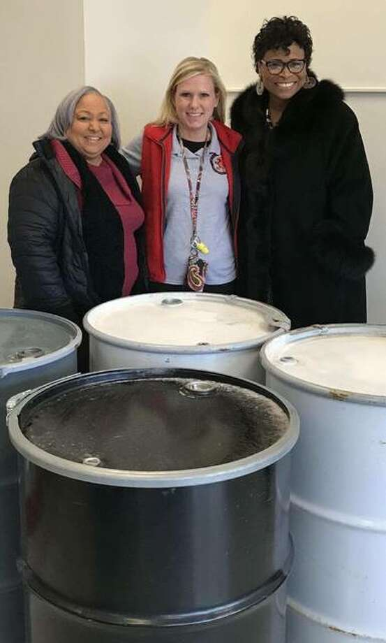 Alderwoman Tammy Smith, 4th Ward; Principal Lanea DeConcini of East Elementary School; and the Rev. Sheila Goins with some of the metal drums the James Killion Beautification Enhancement Committee is having students decorate. The city will place the decorated bins at James H. Killion Park at Salu this spring. Smith and Goins are members of the committee. Photo: For The Telegraph