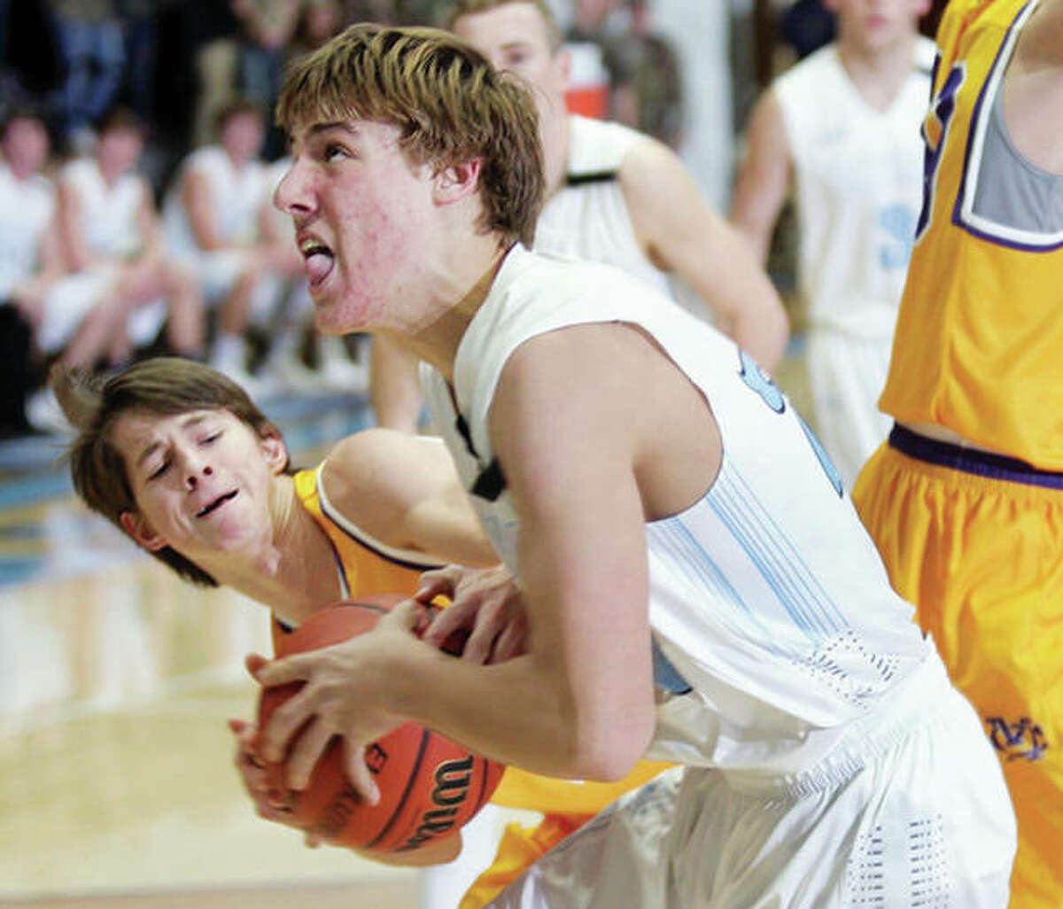 Civic Memorial's Caden Clark (left) tries to steal the ball from Jersey's Matthew Jackson Friday night at Havens Gym in in Jerseyville.