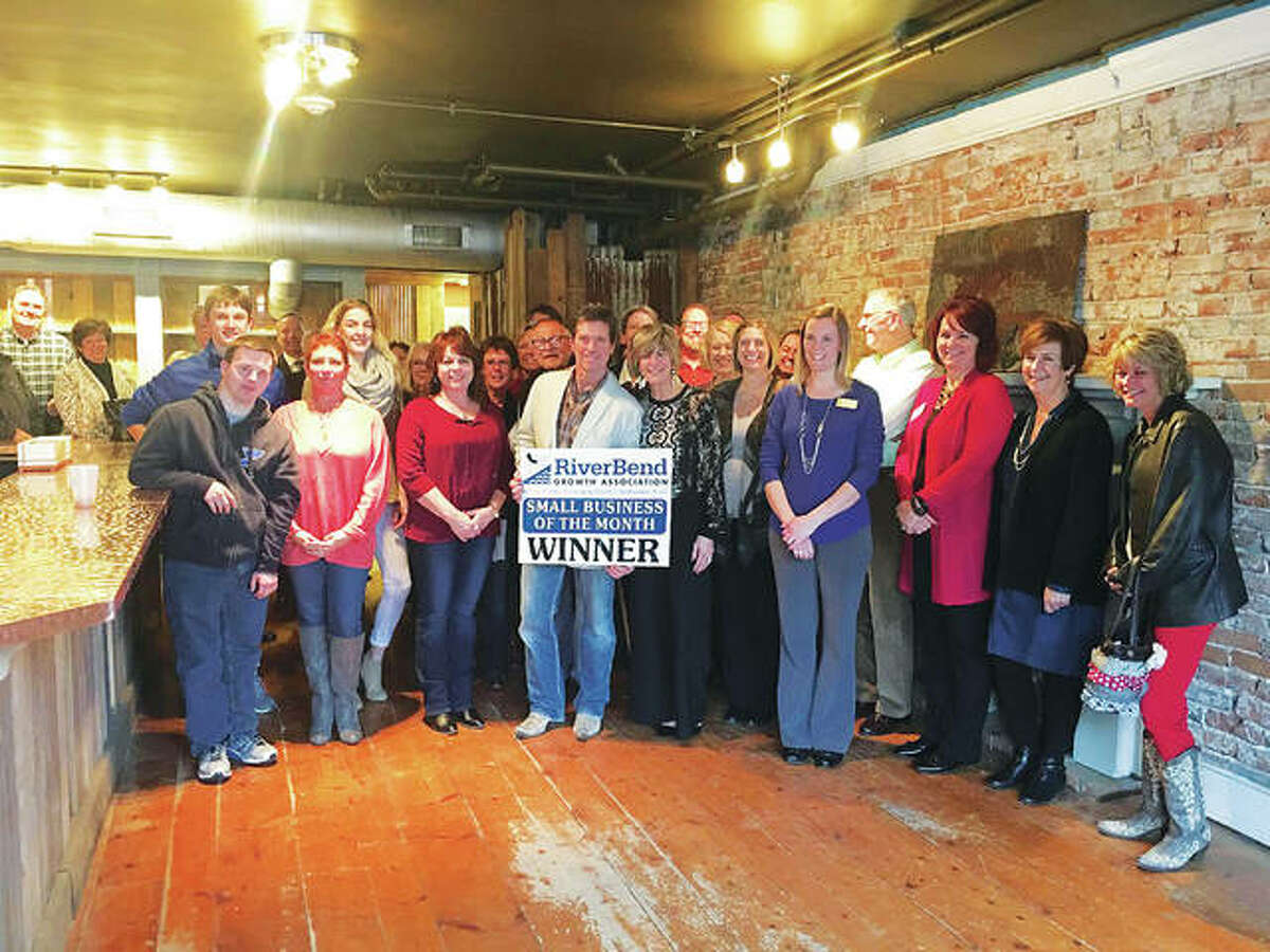 """The RiverBend Growth Association named State Street Market as its January Small Business of the Month. Owners Glenn Beaubien, who goes by """"Beau,"""" holds the sign, next to his wife, Terri Beaubien, right, at the RBGA presentation held in the restaurants new bar space."""