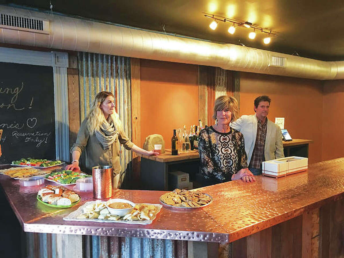 """Aimee Hughes, left, is in charge of the new wine-focused bar at State Street Market, in Downtown Alton, owned by Terri Beaubien, center, and her husband, Glenn Beaubien, right, who goes by """"Beau,"""" all of whom greeted guests who attended the RiverBend Growth Association's January Small Business of the Month presentation. The full bar serves wine, beer and spirits. The restaurant also sells retail wine."""