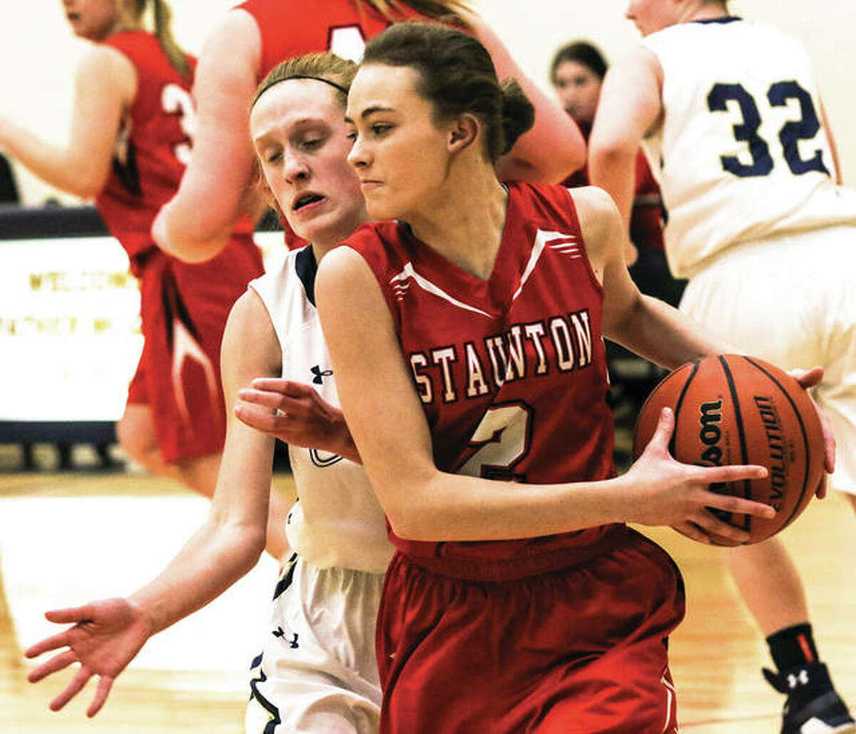 Staunton junior Hali Bandy (front) protects the basketball from defensive pressure by Father McGivney's Anna McKee during a game Thursday in Glen Carbon.