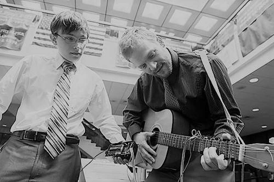 Nicholas Carter, of St. Charles, Mo., and Dan Ashbaugh, of Altamont, demonstrate the usability of their team's LED Learning Guitar. Photo: For The Telegraph