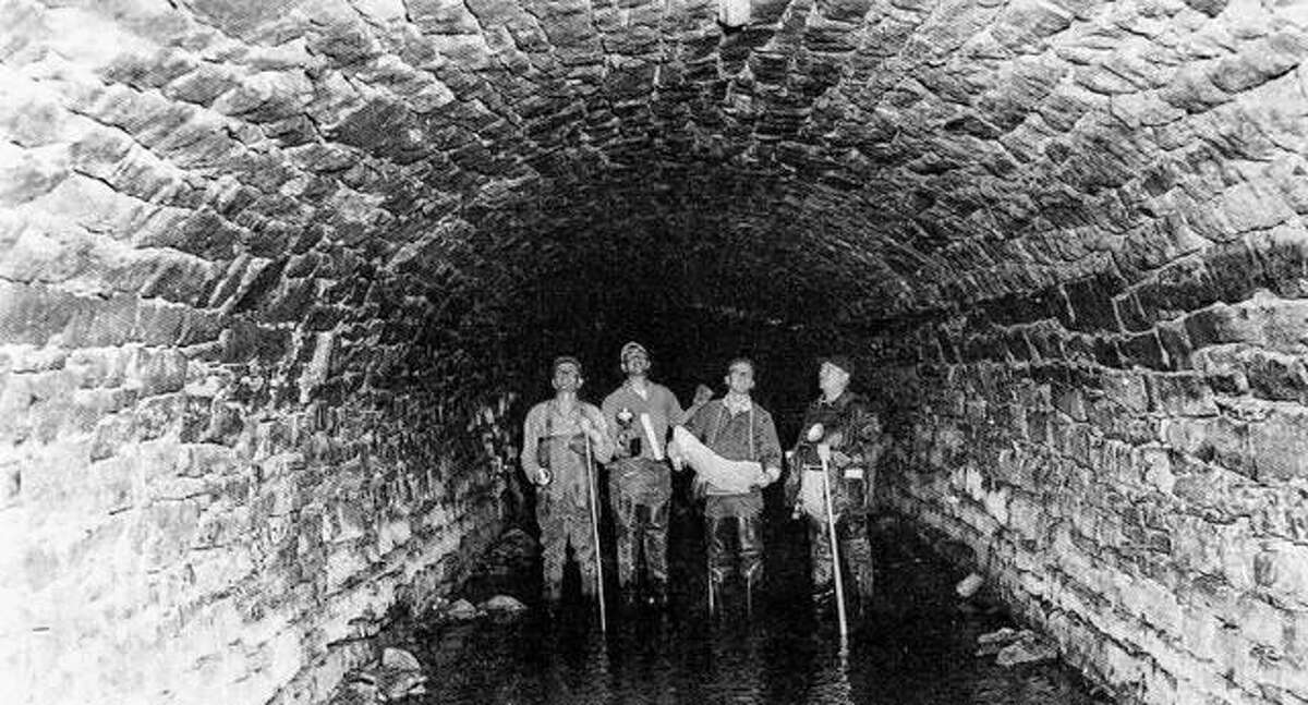 Engineers in the 1950s take a good look at the workmanship in the Piasa culvert that was begun in 1837. The Alton sewer line still runs through the area that is now Piasa Street. In Alton's earliest days, the Little Piasa Creek ran through downtown, dividing the town in two distinct sections. There was only one bridge for a time, at Third Street. Since that time, more bridges and the culvert structure covered the creek channel. At one time, the members of the Whigs Political Party held secret meetings in the culvert.