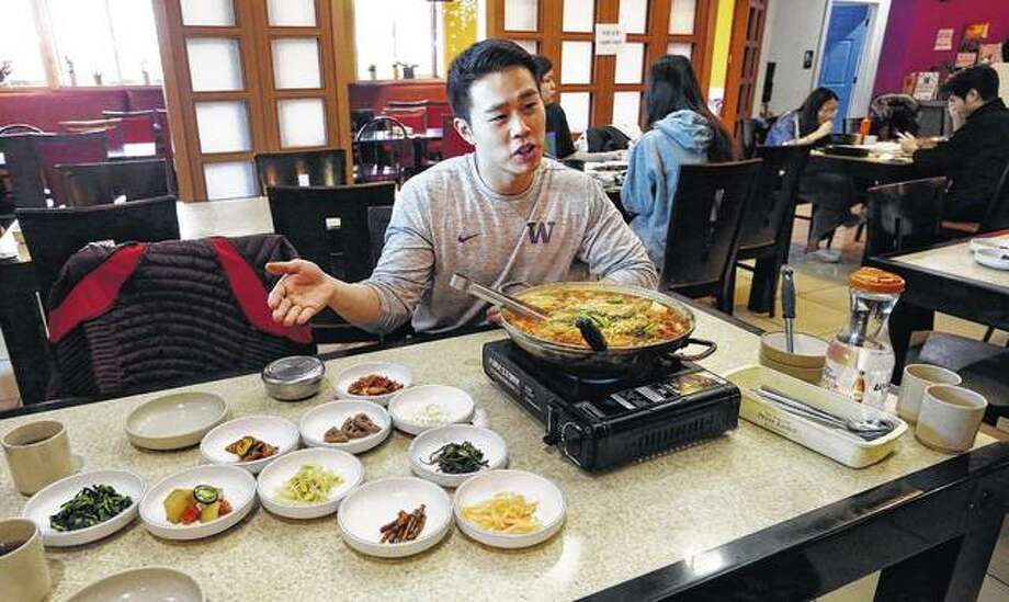 """Server Young Kim talks about the South Korean dish called budae jjigae, or """"army stew,"""" he serves simmering atop a heating plate at a Korean restaurant in Shoreline, Washington. Spam, trout, fried chicken, moon pies and anything slathered in mayonnaise are among the flavors of South Korea's home cooking that might seem just a bit familiar to the U.S. athletes and hordes of westerners preparing to descend on the small Asian country for the 2018 Olympic Winter Games. Photo: Elaine Thompson 