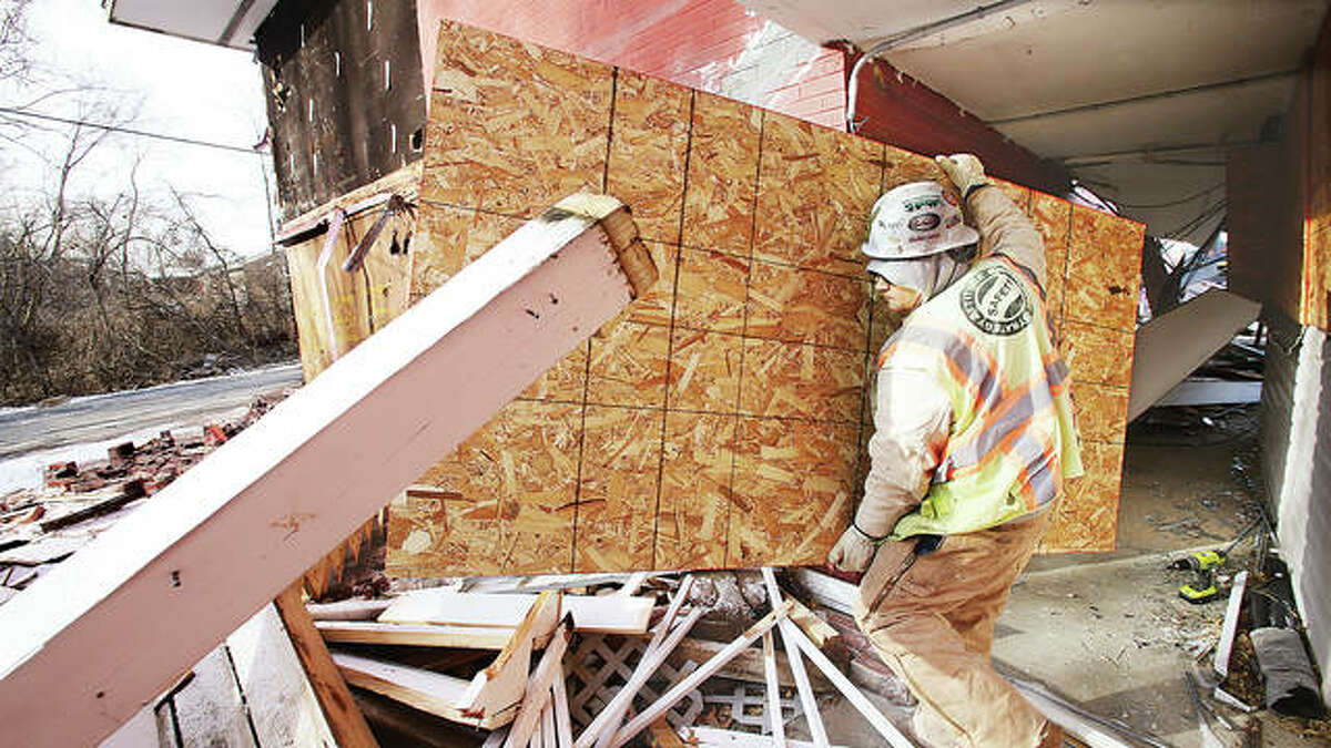 A worker Monday morning removes the boards that were covering the windows of the former Hiway House motel for months as he walks through the rubble which was a second floor set of stairs. It was one of the first things razed at the old multi-building motel.