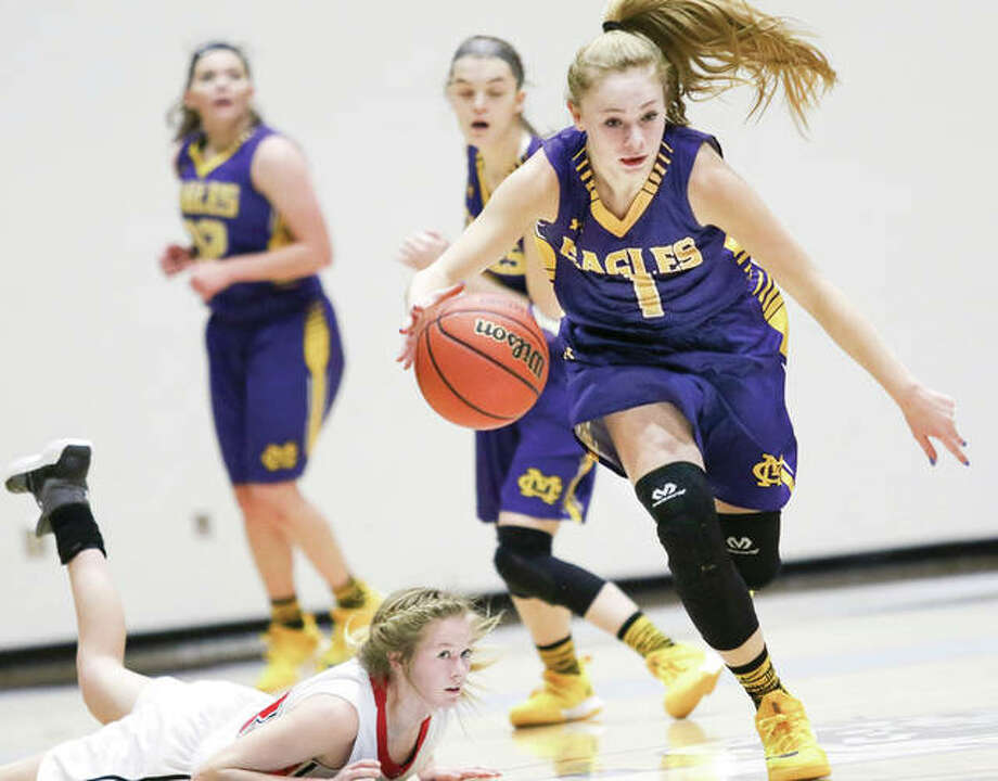 Civic Memorial's Tori Standefer (1) heads upcourt as Calhoun's Junie Zirkelbach (left) watches after falling to the court during play at the Jersey holiday tournament on Dec. 28 in Jerseyville. CM's win Monday night at Mascoutah clinched the MVC title outright for the Eagles, while Calhoun preps for its Carrollton Class 1A Regional opener against Carrollton on Wednesday night. Photo: Nathan Woodside / For The Telegraph