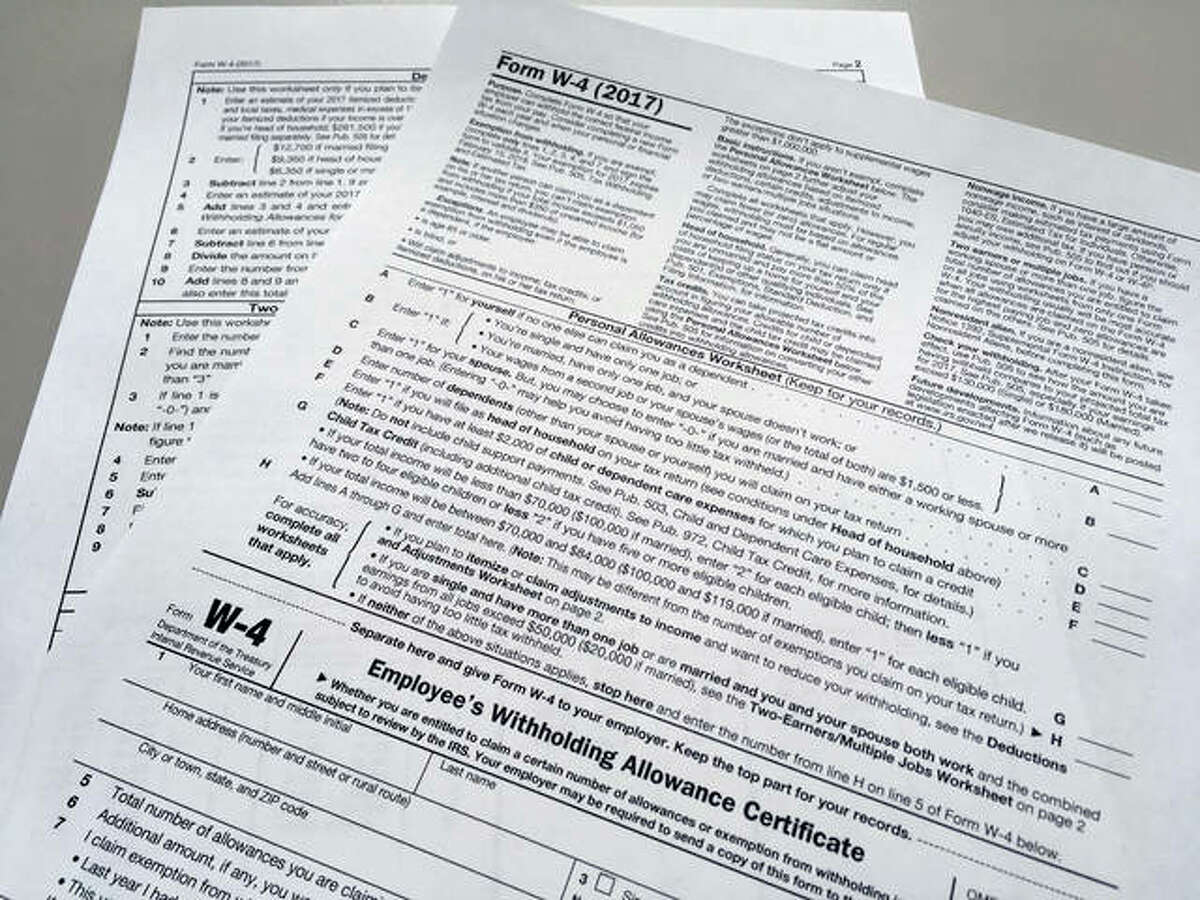 This photo shows an IRS W-4 form on Thursday, Feb. 1, 2018, in New York. Workers are starting to see more take-home pay as employers implement the new withholding guidelines from the IRS. How much extra cash depends on several factors, such as workers' income, how often they are paid and the number of withholdings allowances they claim on their IRS Form W-4 with their employer.