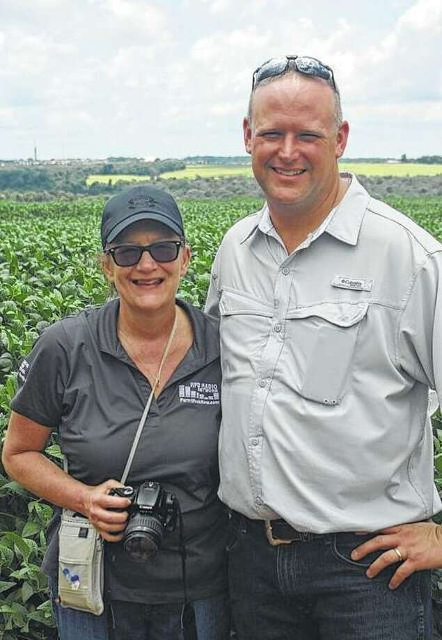 Rita Frazer, director of radio for the Illinois Farm Bureau, stands with Chad Schutz, a rural White Hall farmer, in a soybean field in Brazil. They were among 13 Illinois Farm Bureau members who visited farms in Brazil and Argentina.